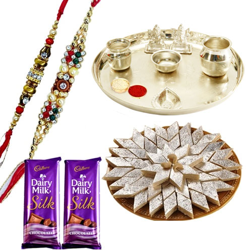 An Exclusive Gift Hamper with Silver Plated Thali, Delicious Kaju Katli and Gift Voucher from Raymond along with 2 free Rakhi,Roli Tika and Chawal